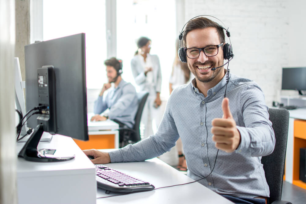 Happy male customer service operator showing thumb up in office
