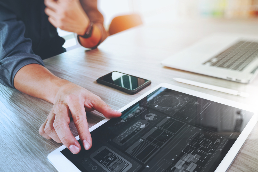 Website designer working digital tablet and computer laptop with smart phone and graphics design diagram on wooden desk as concept